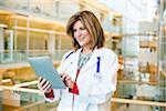 Porträt eines Arztes halten ein Tablettgerät.
