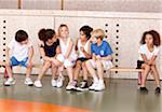Young schoolchildren sitting on bench in gym