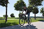 Man riding bicycle on rural road