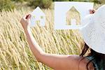 Femme tenant maison de papier découpé outs