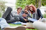 Étudiants à l'aide de téléphone portable sur l'herbe
