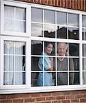 Nurse and older man at window