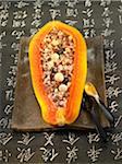 La moitié d'une papaye farci de riz sauvage