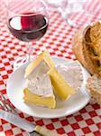 Teile des Camembert, Brot und ein Glas Rotwein