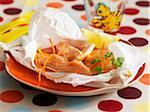 Saumons et fines tranches de carottes cuites dans du papier ciré