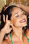 Schönes Mädchen im Pool mit Spritzwasser