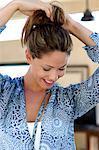 Beautiful girl tying up her hair