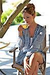 Schöne Mädchen sitzen außerhalb Kräutertee trinken