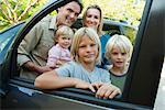 Family posing beside car, looking through open window, portrait