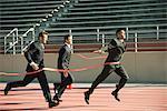 Businessman crossing finish line in race