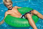 Boy relaxing on float in pool