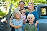 Family posing beside car, portrait