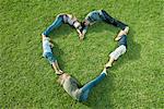 Menschen liegen auf Gras in Form von Herzen positioniert