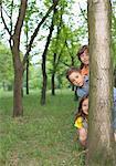 Three children behind a tree trunk