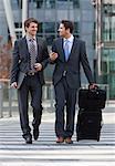 Two smiling businessmen using crosswalk