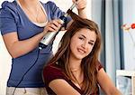 Teenage girl getting hair dressed