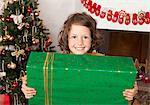 Girl holding present at Christmas tree