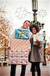 Ein junges Paar halten verpackt Geschenke außerhalb.