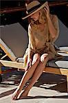 Beautiful blonde woman applying suncream outside