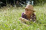 Femme souriante assise dans le champ de blé