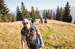 Homme avec pack de randonnée sur la colline herbeuse