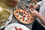 Chef garnishing pizza in kitchen