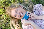 Close-up Portrait de femme couchée sur l'herbe holding Cell Phone