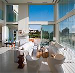 Salle de séjour double hauteur avec canapé blanc et des chaises dans Rishpon dans le District Centre d'Israël. Architectes : Irit Exselrod