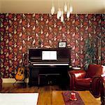 Fauteuil en cuir en face de piano contre le papier peint à motifs. Conçu par conçu par Margaret Gamble