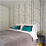 Coussins bleus sur lit contre le mur avec papier peint arbre