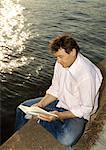Homme lisant livre sur le front de mer