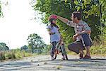 Père et fille avec casque de vélo en plein air