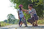 Père fermant le casque de sa fille sur une moto