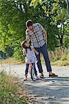 Père et fille sur le vélo à l'extérieur
