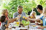 Multi-generation family toasting with orange juice outdoors, portrait