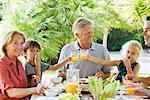 Multi-generation family enjoying meal outdoors