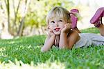 Kleines Mädchen liegend auf Gras, nachschlagen