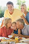 Family having breakfast outdoors, grandparents kissing granddaughter's cheeks, portrait