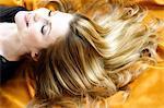 Porträt einer jungen Frau liegend, lange Haare auf gelb Textil Stoff