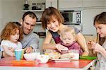Couple and 3 children having breakfast
