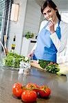 Jeune femme souriante de cuisine, dégustation de tranches de concombre