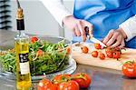 Femme faisant une salade, hacher les tomates, gros plan