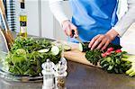 Femme faisant une salade, concombre, close-up à découper