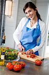 Jeune femme souriante, faire une salade, hacher les tomates