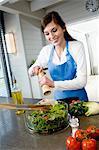 Jeune femme souriante assaisonner une salade