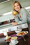 Smiling woman holding fruit juice