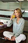 Woman drinking fruit juice, cross-legged