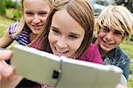 2 adolescentes souriantes et le garçon à l'aide du téléphone-appareil photo, à l'extérieur