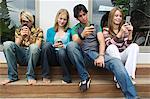 2 teenage boys and 2 teenage girls using their mobile phones