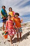 Parents et deux enfants marchant sur la plage, en plein air